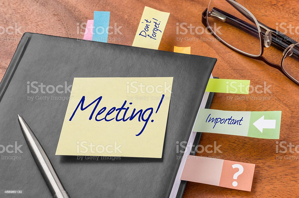 Planner with sticky note - Meeting stock photo