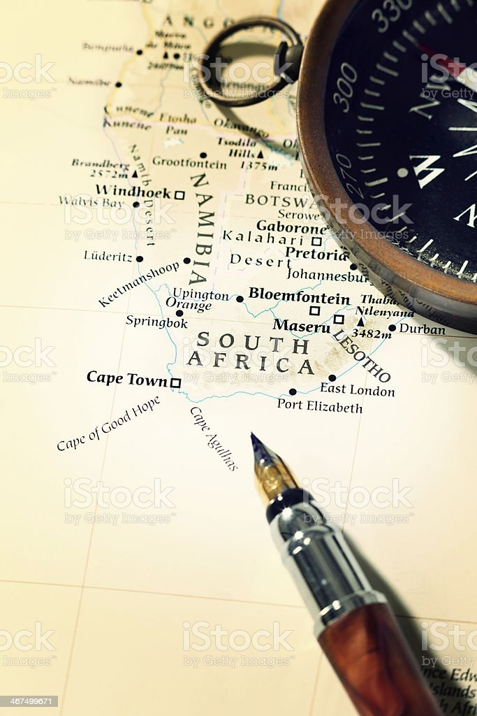 A compass and a pen rest on a map of western South Africa, Botswana,...