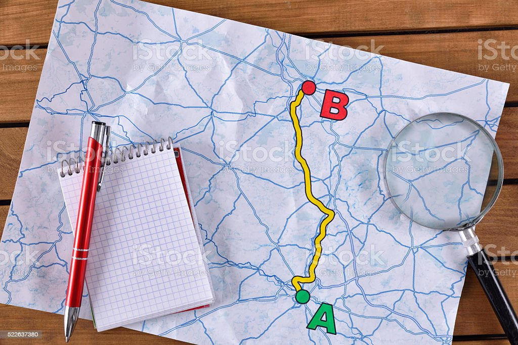 Planning a path on a paper on a wooden table stock photo
