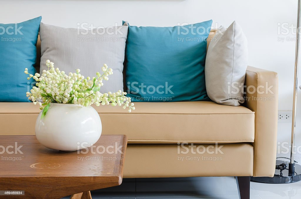plant in ceramic vase on wooden table with modern sofa stock photo