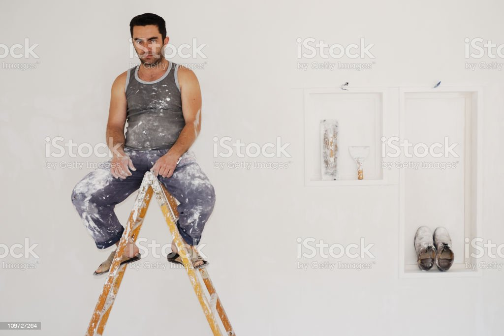 Plaster worker sitting on the ladder royalty-free stock photo