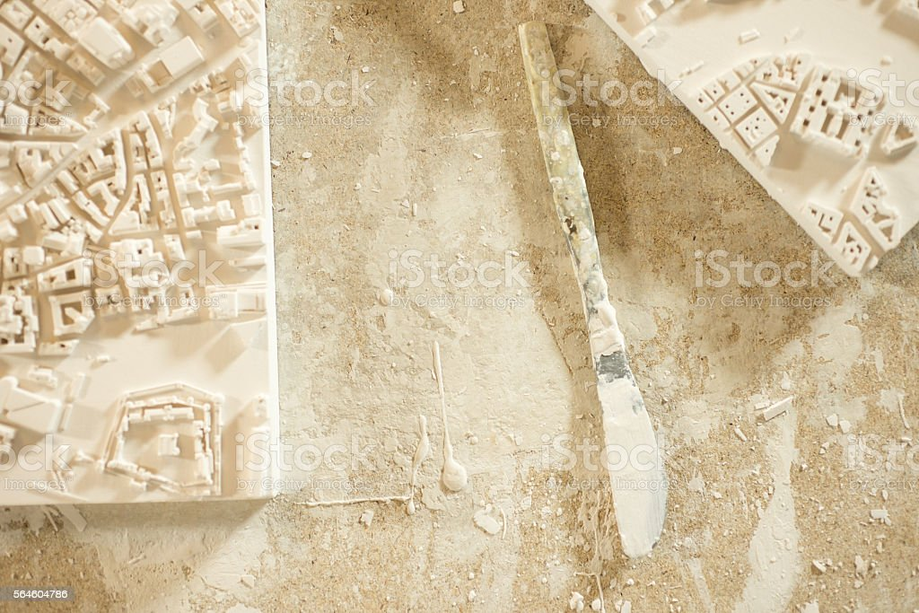 Plaster-Coated Knife Between 3D City Map Plaster Models stock photo