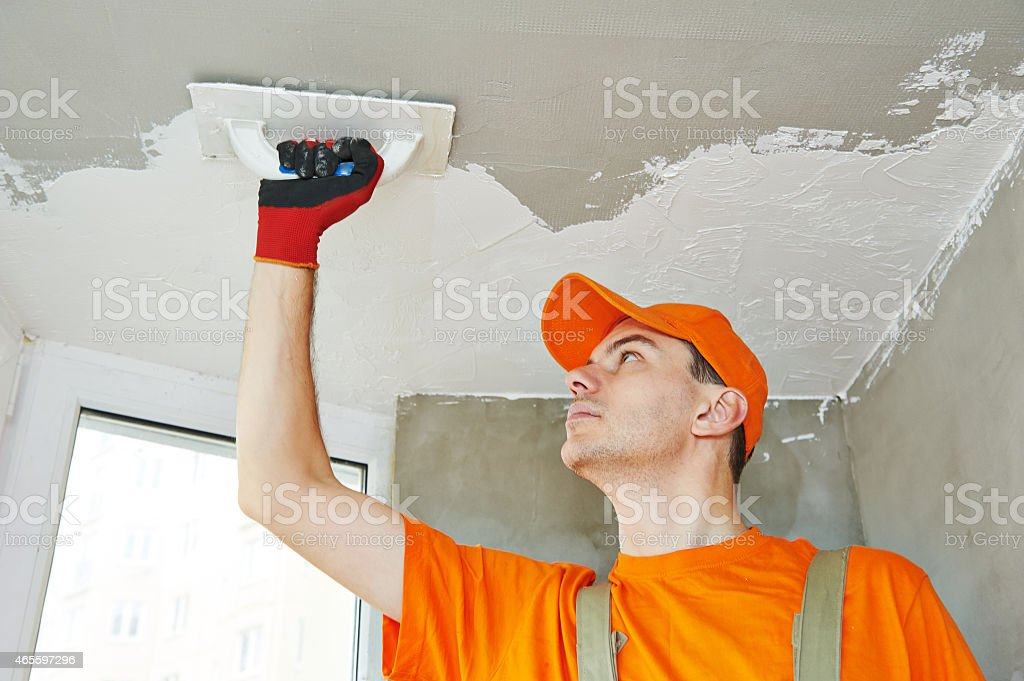 Plasterer at indoor ceiling work stock photo