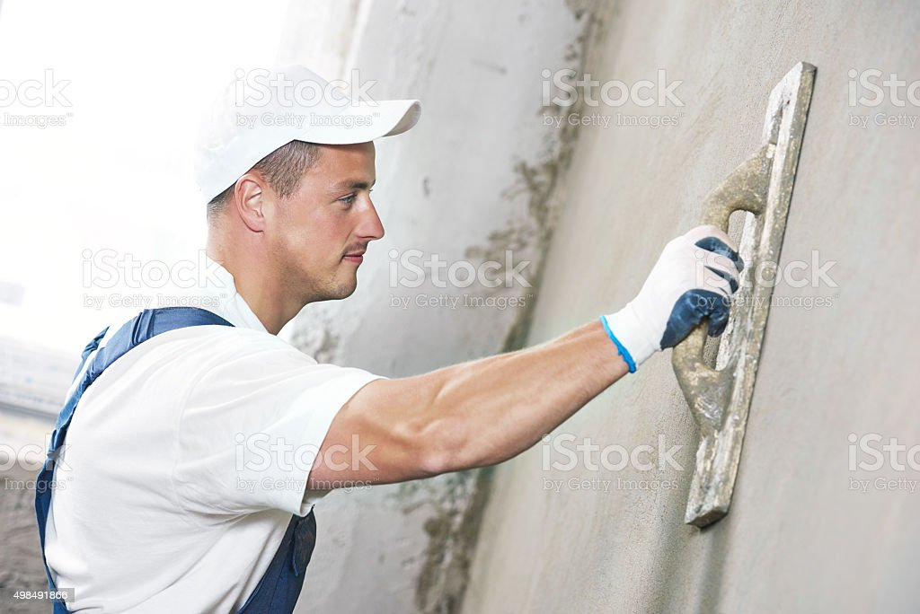 Plasterer at indoor wall renovation stock photo