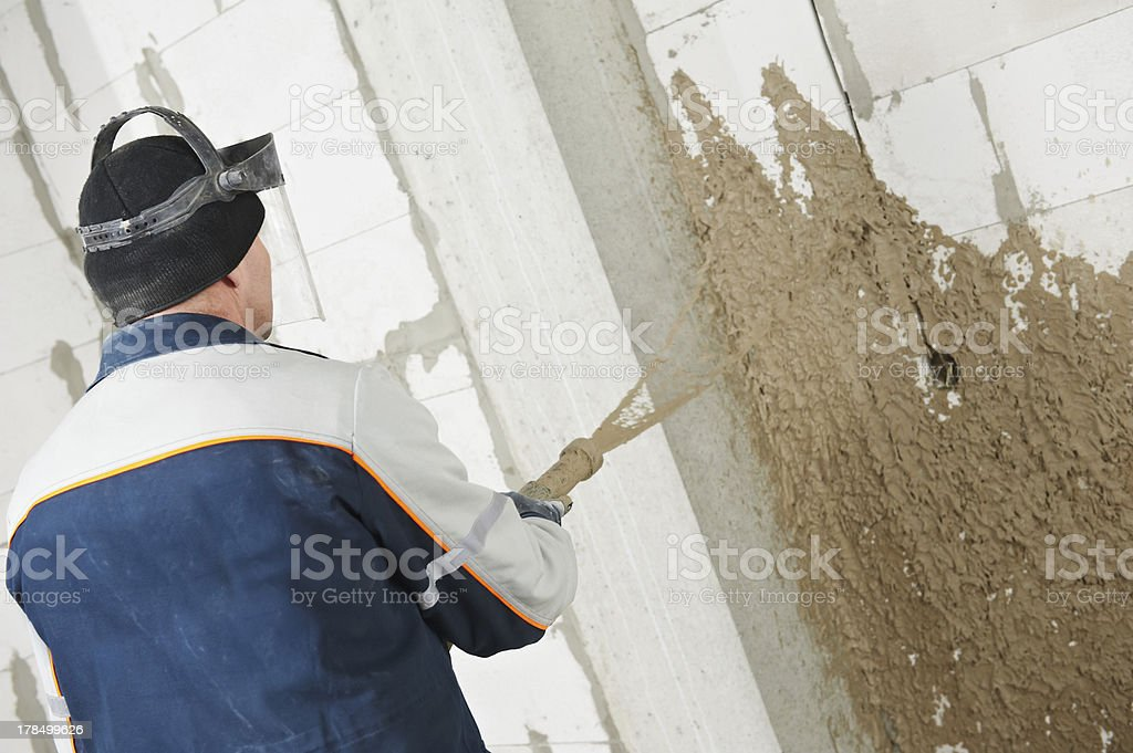 Plasterer at stucco work with liquid plaster royalty-free stock photo