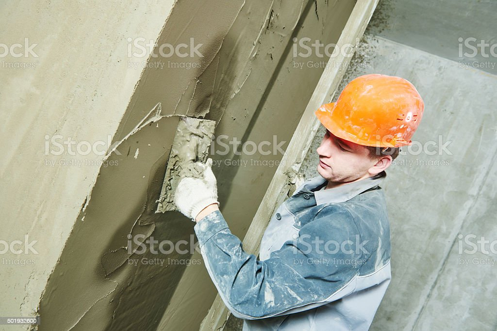 Plasterer at work with wall stock photo