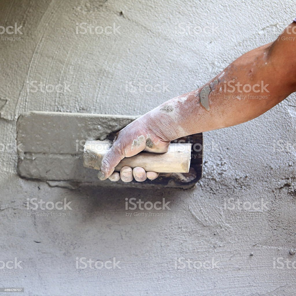 plasterer concrete worker at wall of house construction royalty-free stock photo