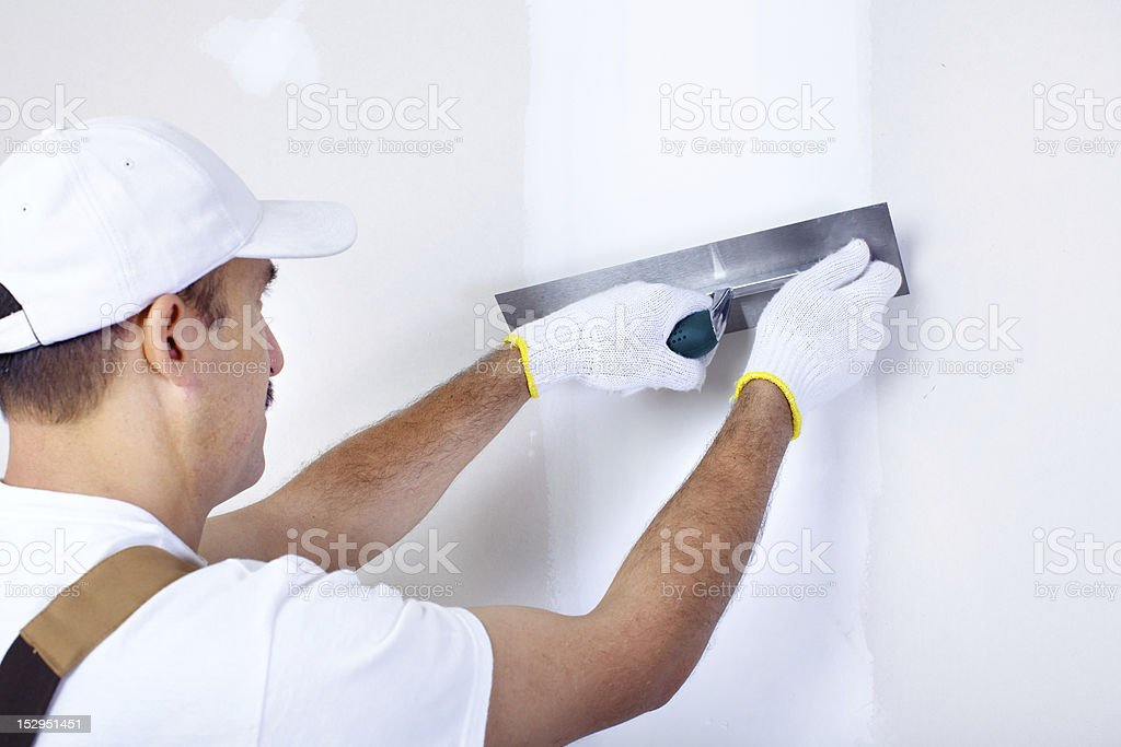 A plasterer plastering a white wall royalty-free stock photo