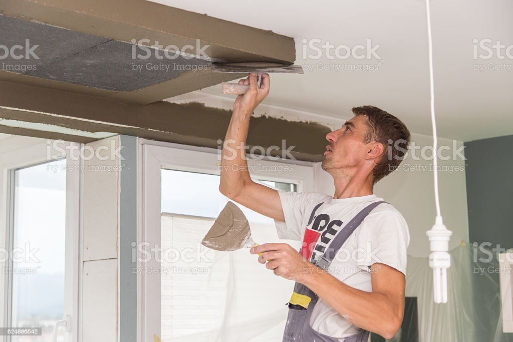 Plasterer renovating indoor walls and ceilings. Finishing works. stock photo