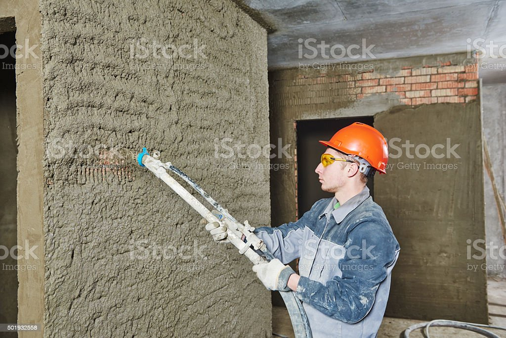 Plasterer spraying plaster on wall stock photo