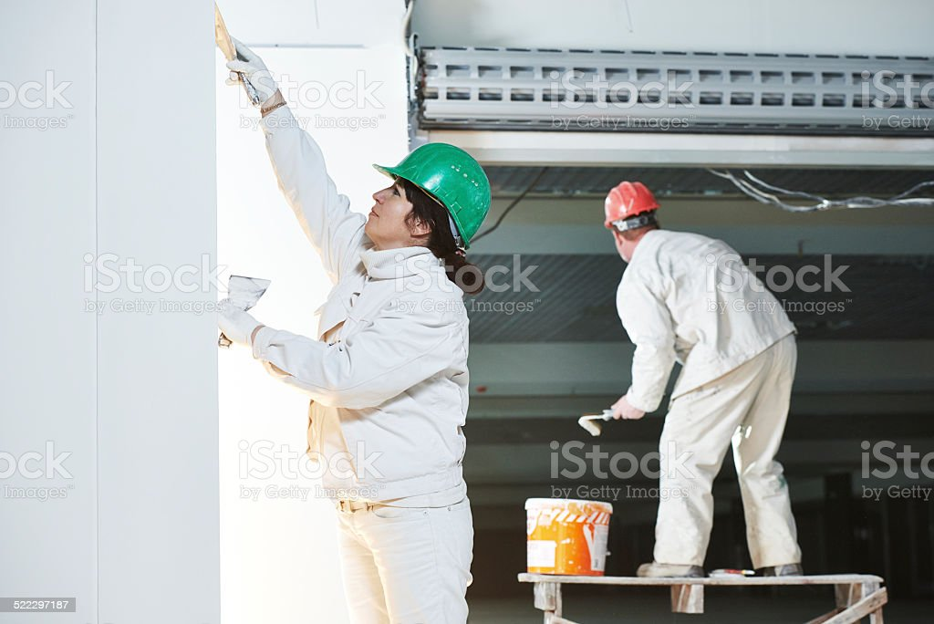 Plasterers at indoor wall work stock photo
