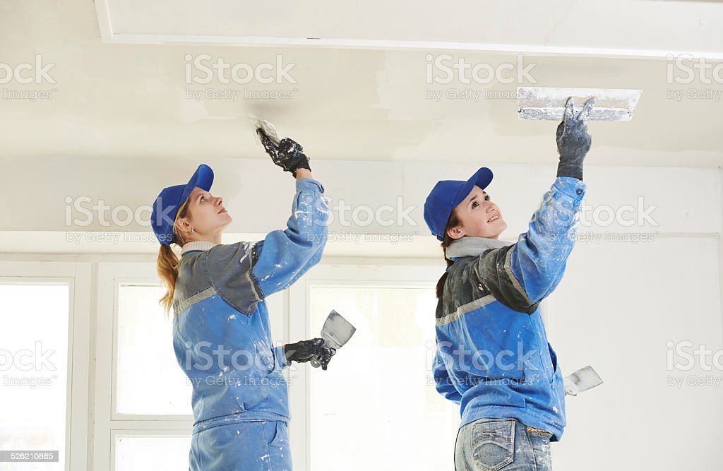 Plastererst at indoor ceiling work stock photo