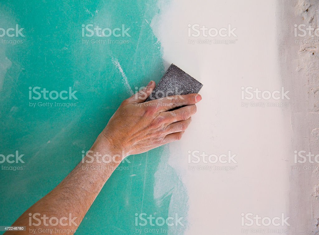 plastering man hand sanding the plaste in drywall seam stock photo