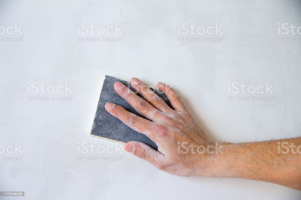 plastering man hand sanding the plaster stock photo