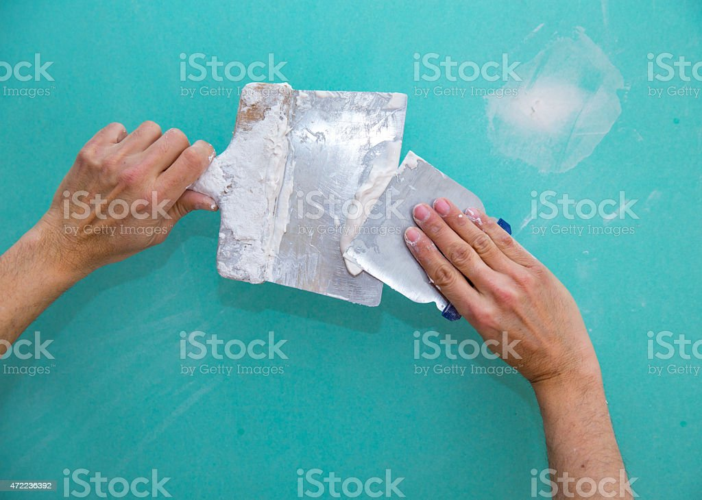 Plastering man hands with plaste on drywall plasterboard stock photo