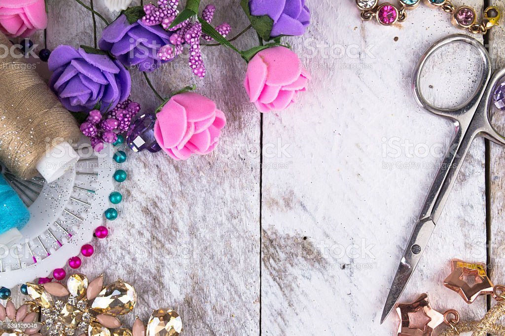 Plastic berries, flowers, beads and instruments on white wood stock photo