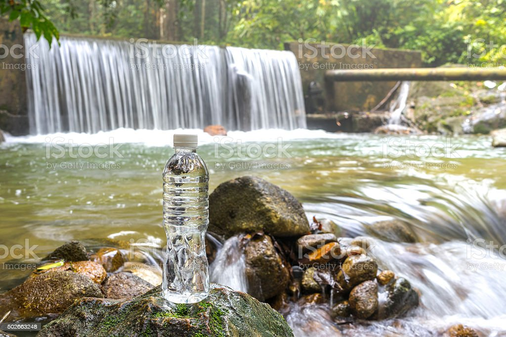 Plastic bottle and tropical waterfall stock photo