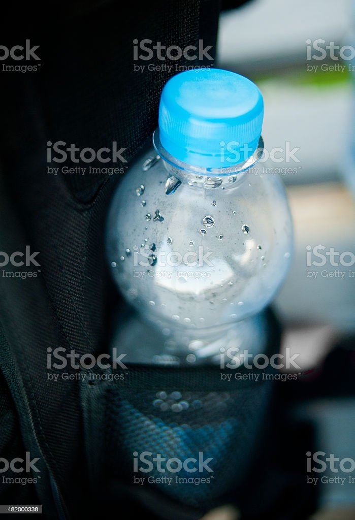 plastic bottle of water in pocket of backpack stock photo