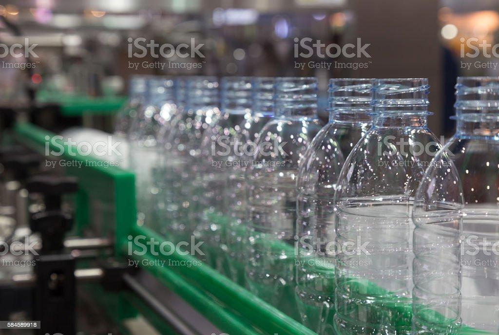 plastic bottle on factory line machine, selective focus stock photo