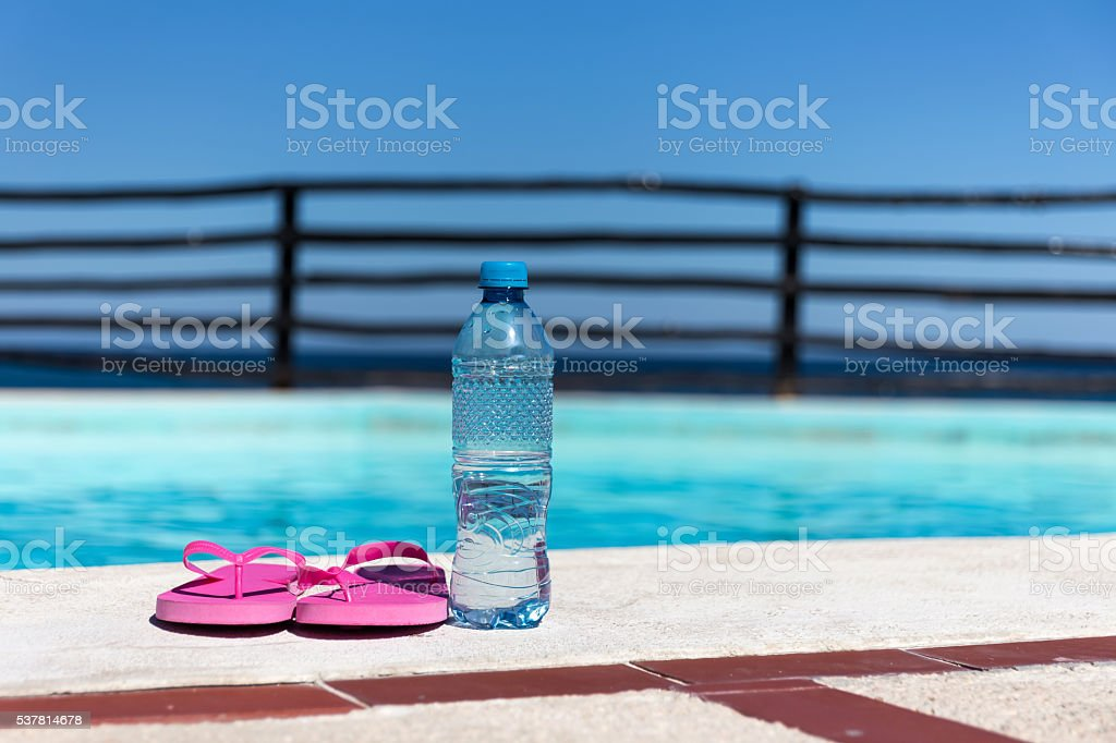 Plastic bottle with pure water and slippers near swimming pool stock photo