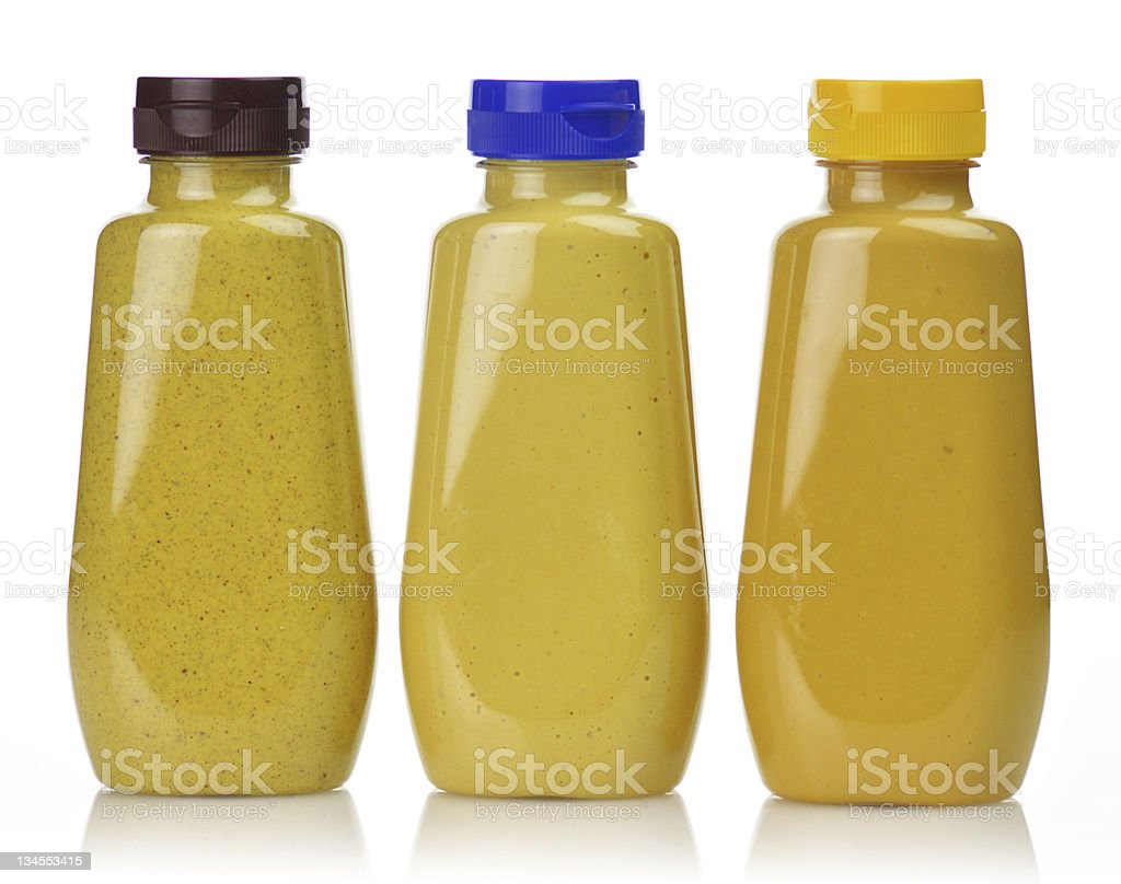 3 plastic bottles of different mustards with colored tops stock photo