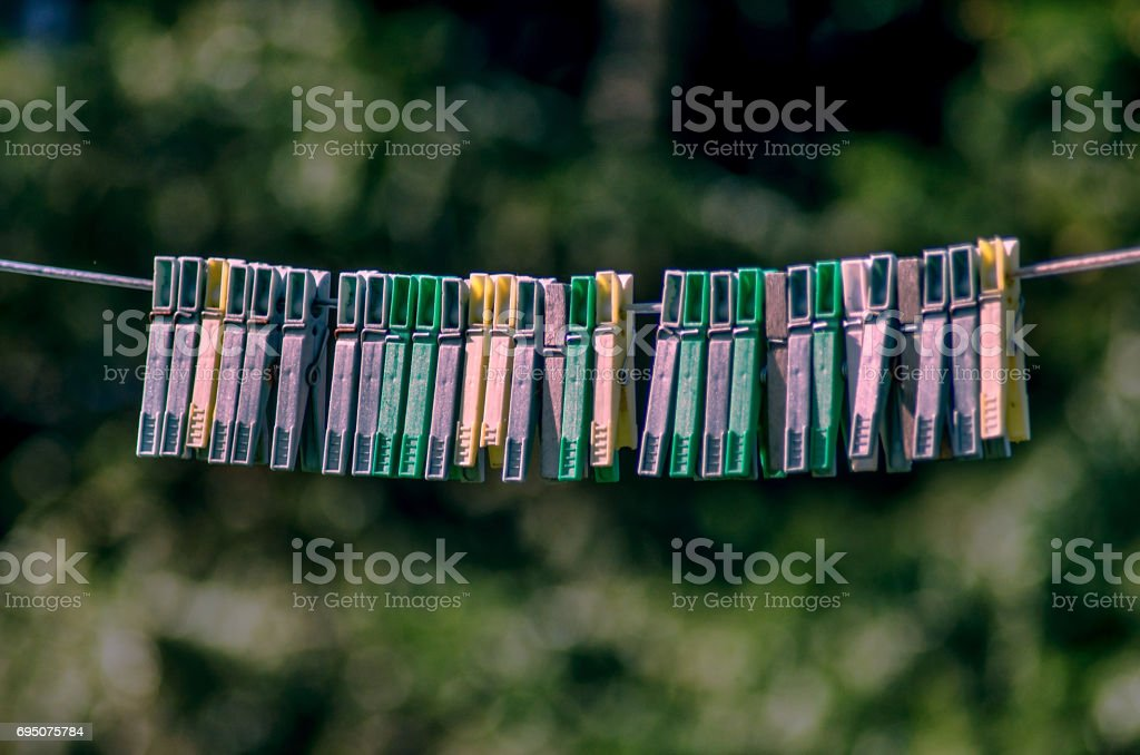 Plastic clothes pins hanging on string rope stock photo