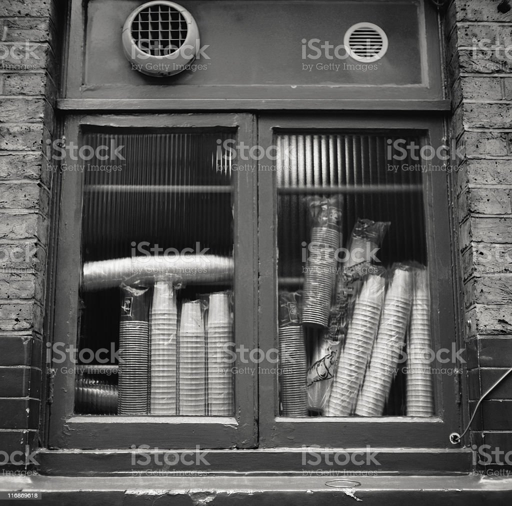 Plastic cups stacked behind a pub window pane royalty-free stock photo