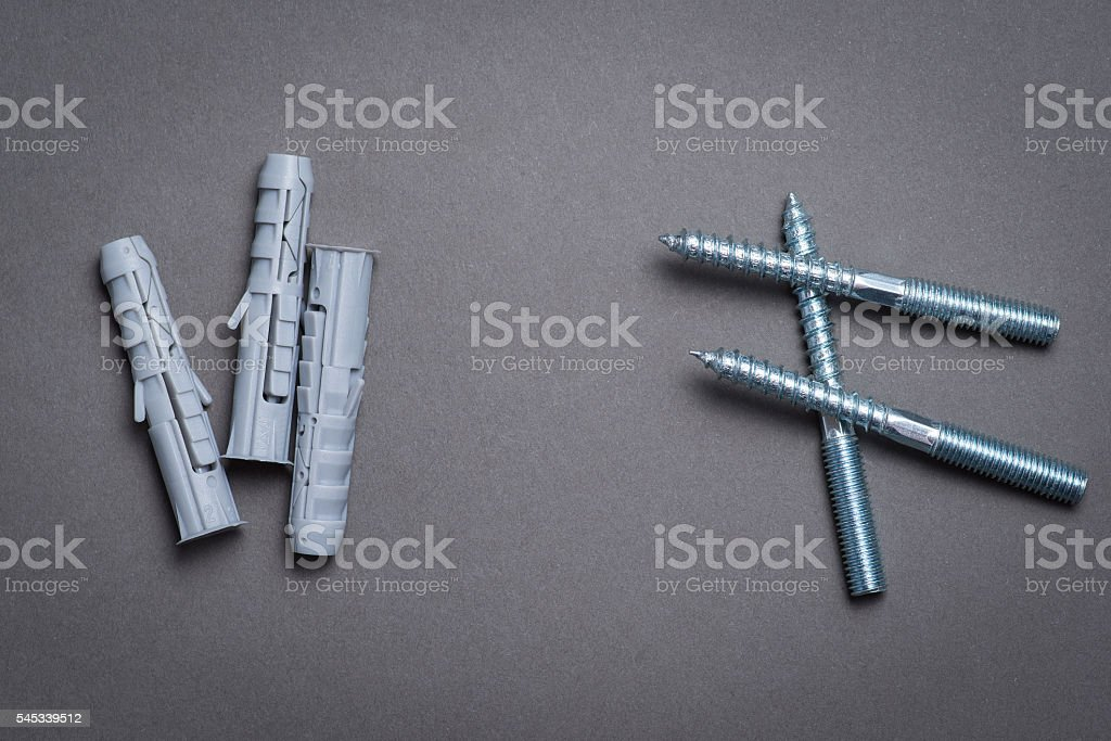 Plastic dowels and screws on dark grey surface stock photo