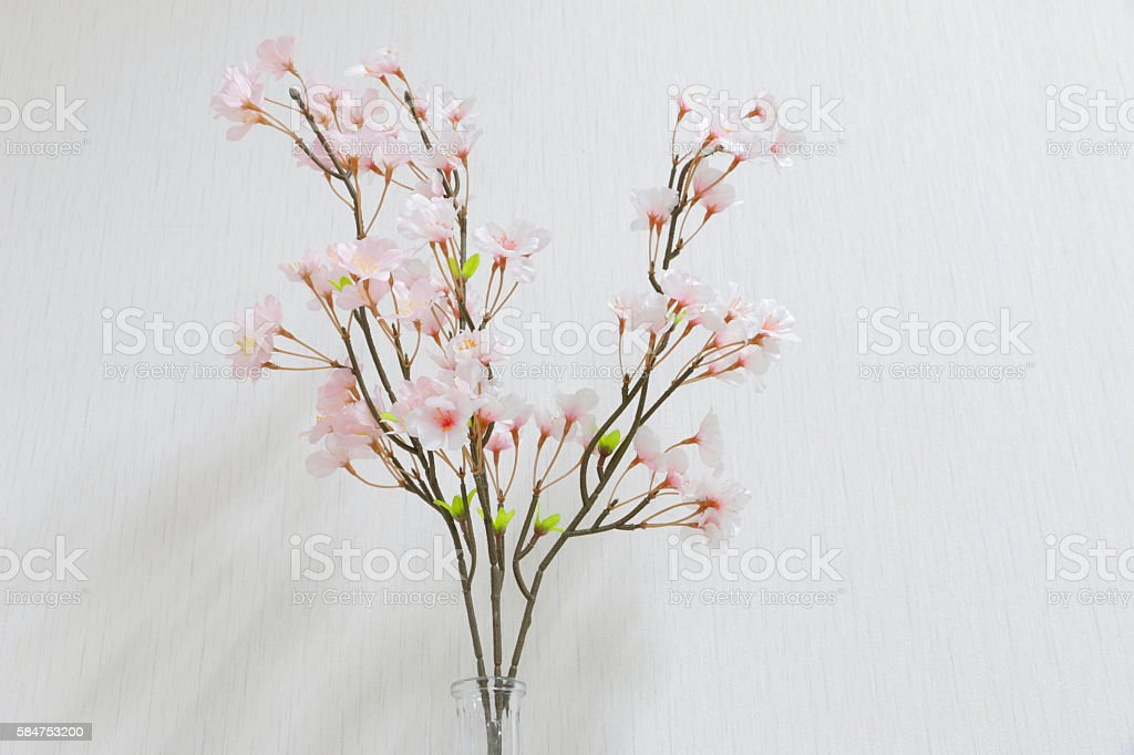 Plastic flowers in a vase on a dark gray background stock photo