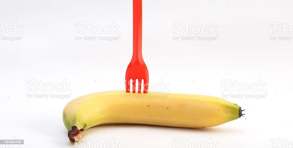 Plastic fork on a ripe banana stock photo