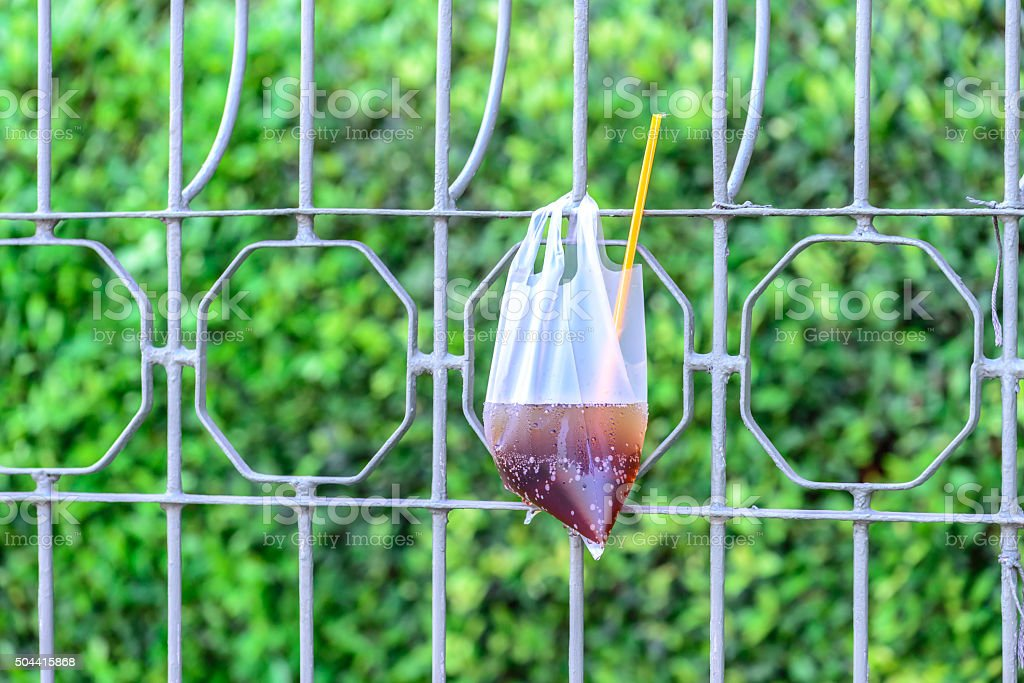 Plastic garbage bag used was left on fence in city. stock photo