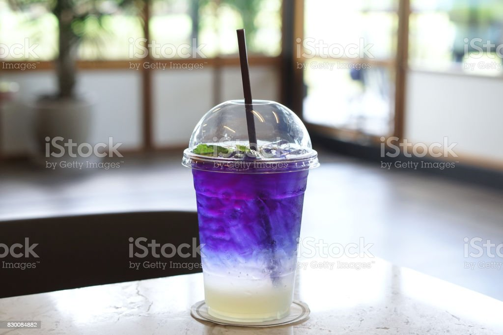 Plastic glass of iced butterfly pea tea with lemon on wooden table, Relax with Thai herbal drink for healthy life. stock photo