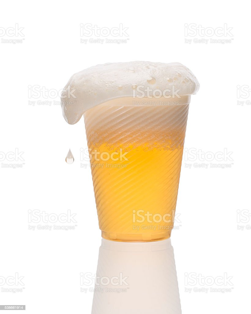 Plastic glass of overflowing lager beer. Home brewing. stock photo