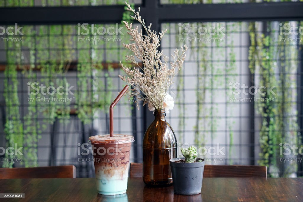 A plastic glass of refreshing iced chocolate mixed with pastel peppermint on table. stock photo