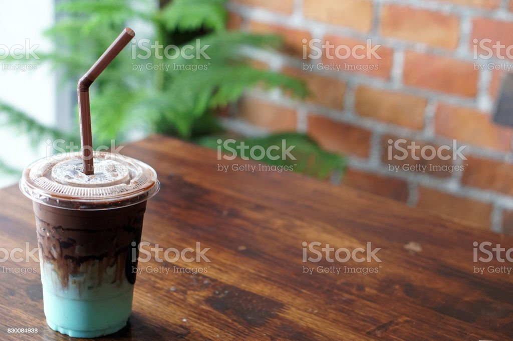 A plastic glass of refreshing iced chocolate mixed with pastel peppermint on wooden table. stock photo