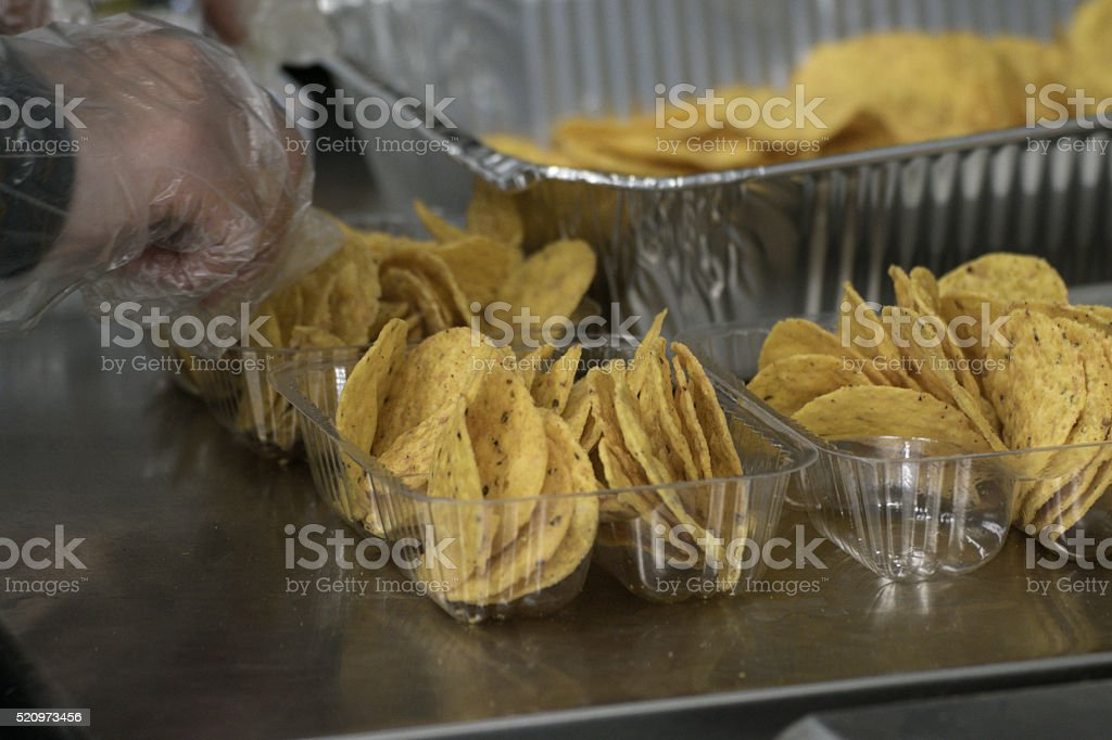 Plastic Gloved Hand Preparing Concession Nachos Tortilla Chips Snack Food stock photo