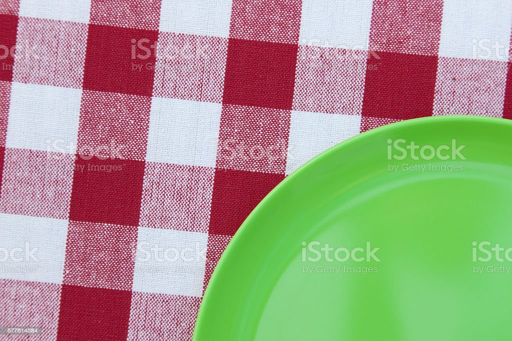 Plastic green plate on red and white plaid tablecloth stock photo