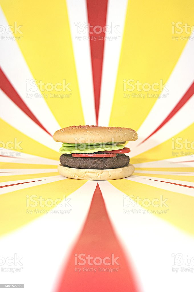 Plastic Hamburger with tomato, lettuce on red and yellow background royalty-free stock photo