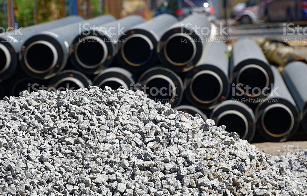 Plastic industrial drain pipe next to a pile of gravel. stock photo