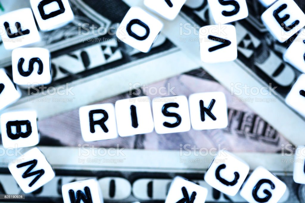 """Plastic letter beads spelling """"Risk"""" on us dollars background, financial or currency risk concept stock photo"""