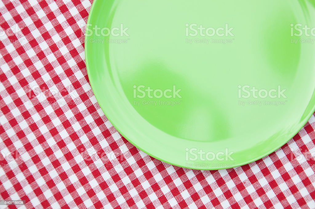 Plastic lime green plate on red and white plaid tablecloth stock photo