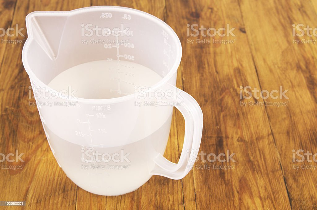 Plastic Measuring Jug With Water On Wooden Surface stock photo