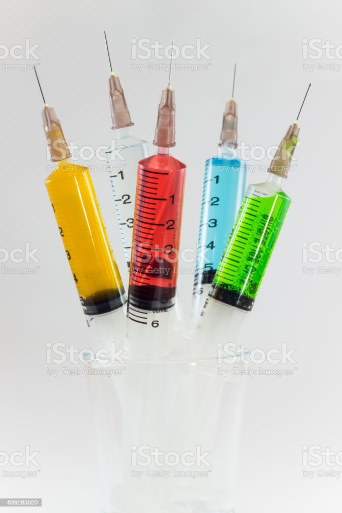 plastic medical syringes containing multicolor solutions in medicine glass stock photo