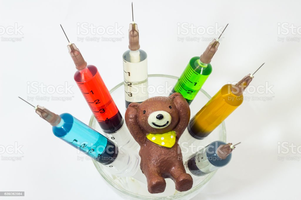 Plastic medical syringes containing multicolor solutions with clay teddy bear stock photo