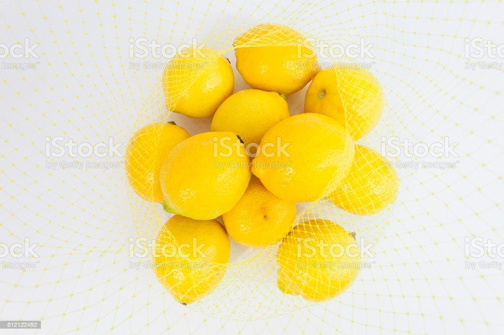 Plastic Mesh Bag full of Lemons stock photo
