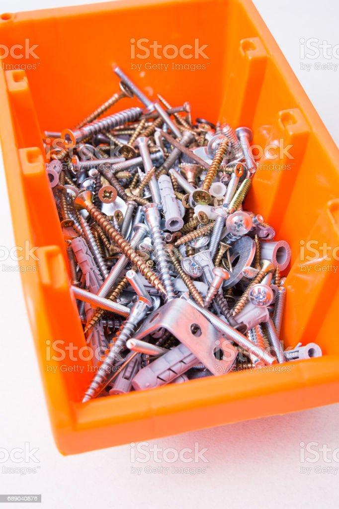 Plastic orange box with screws stock photo