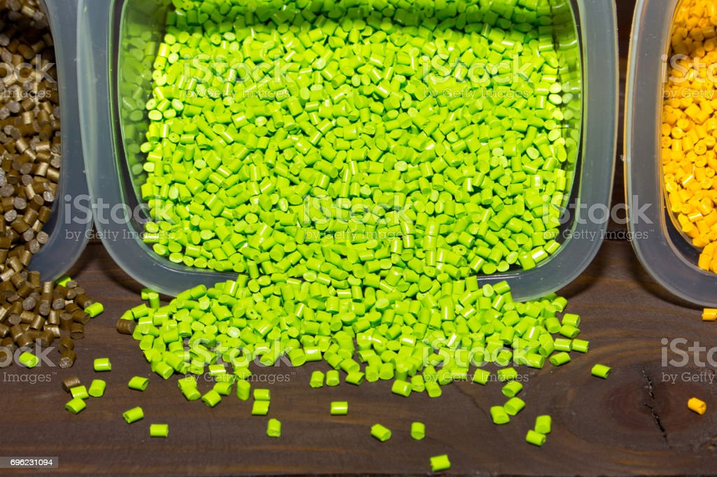 Plastic pellets are poured from a measuring container on laboratory table stock photo