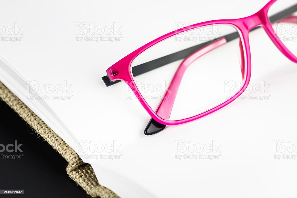 Plastic pink spectacles on open book stock photo