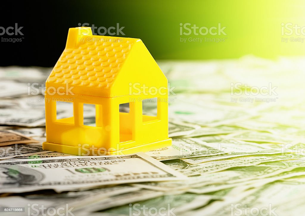 Plastic play house sitting on stacks of US dollars stock photo