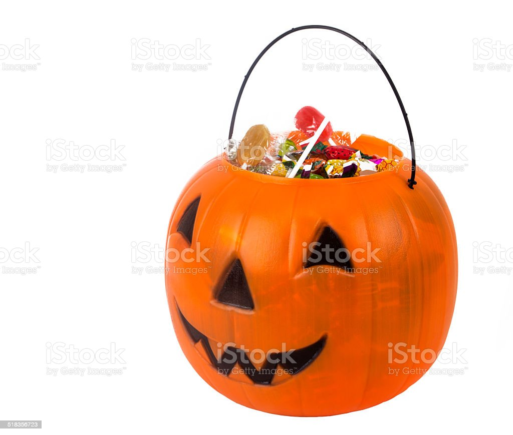 Plastic pumpkin filled with candy stock photo